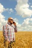 Agricoltore glabro in vetri che stanno in un giacimento di grano e che parlano sul telefono Foto verticale Fotografia Stock