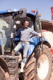 Agricoltore in grande trattore delle ruote Fotografia Stock