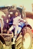 Agricoltore in grande trattore delle ruote Immagine Stock