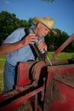 Agricoltore Greases il suo Hay Baler Fotografia Stock Libera da Diritti