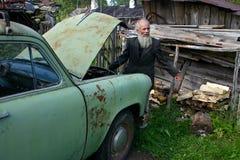 Agricoltore grigio-barbuto anziano che sta vicino all'annata verde chiaro c Immagini Stock Libere da Diritti