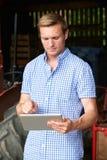 Agricoltore Holding Digital Tablet che sta nel granaio con vecchio Fashione Fotografie Stock