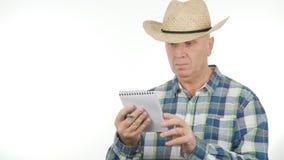 Agricoltore Image Use un libro tascabile che legge le note fotografie stock