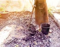 Agricoltore lavorando nelle piante di giardino con la scavatura di zappatura Fotografia Stock