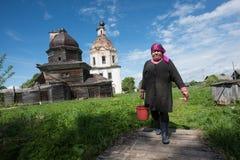 Agricoltore locale con il secchio dello zinco su un fondo della chiesa Fotografie Stock Libere da Diritti