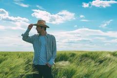 Agricoltore maschio che cammina attraverso il giacimento di grano Fotografia Stock