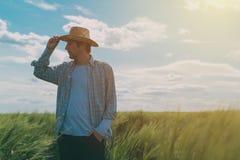 Agricoltore maschio che cammina attraverso un giacimento di grano verde Fotografia Stock Libera da Diritti