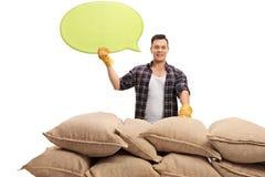Agricoltore maschio che posa dietro i sacchi della tela da imballaggio con il fumetto Fotografia Stock