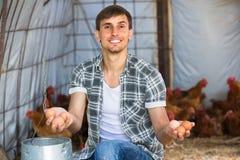 Agricoltore maschio che seleziona le uova fresche in gabbia Fotografia Stock Libera da Diritti