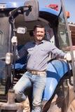 Agricoltore maschio che sta con il grande trattore Immagini Stock