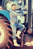 Agricoltore maschio felice che sta con il grande trattore Immagine Stock