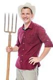 Agricoltore maschio felice con le forcelle su bianco Immagini Stock