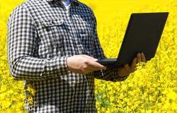 Agricoltore maschio - uomo d'affari che tiene un computer portatile su un campo di canola di fioritura giallo, primo piano Fotografia Stock