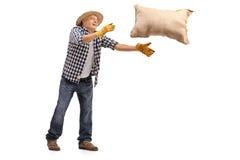 Agricoltore maturo che getta un sacco della tela da imballaggio Fotografia Stock