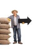 Agricoltore maturo che si appoggia mucchio dei sacchi della tela da imballaggio e che tiene un arr Immagine Stock Libera da Diritti