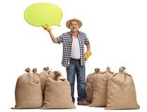 Agricoltore maturo che sta fra i sacchi della tela da imballaggio e che tiene discorso b Immagini Stock Libere da Diritti