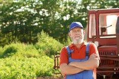Agricoltore maturo che sta trattore vicino Fotografia Stock