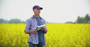 Agricoltore maturo Writing In Clipboard al campo coltivato seme di ravizzone archivi video