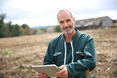 Agricoltore moderno che sta nel campo con la compressa Fotografia Stock