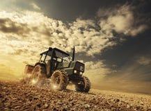 Agricoltore nei campi che guidano un trattore Fotografia Stock