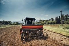 Agricoltore nei campi che guidano un trattore Immagini Stock