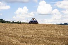 Agricoltore nei raccolti della semina del trattore al campo Immagine Stock