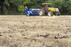 Agricoltore nei raccolti della semina del trattore al campo Fotografia Stock