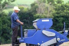 Agricoltore nei raccolti della semina del trattore al campo Fotografie Stock Libere da Diritti