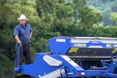 Agricoltore nei raccolti della semina del trattore al campo Immagini Stock