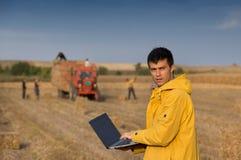 Agricoltore nel campo con il trattore nel fondo Fotografia Stock Libera da Diritti
