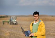 Agricoltore nel campo durante l'imballaggio Fotografie Stock