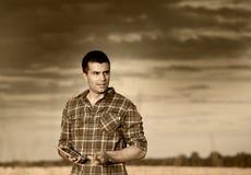 Agricoltore nel giacimento di grano al tramonto di estate Immagine Stock Libera da Diritti