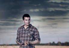 Agricoltore nel giacimento di grano al tramonto di estate Fotografia Stock