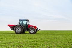 Agricoltore nel giacimento di grano di fertilizzazione del trattore alla molla con npk Fotografia Stock
