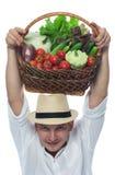 Agricoltore nel raccolto in un canestro sulla sua testa Fotografia Stock