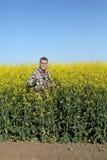 Agricoltore o agronomo nel giacimento sbocciante del seme di ravizzone Fotografie Stock Libere da Diritti