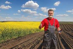 Agricoltore o agronomo nel giacimento sbocciante del seme di ravizzone Fotografie Stock