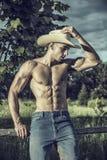 Agricoltore o cowboy sexy accanto al giacimento del fieno Fotografia Stock