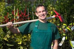 Agricoltore o giardiniere che posa con la pala in giardino Immagine Stock
