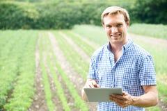 Agricoltore On Organic Farm che per mezzo della compressa di Digital Fotografia Stock