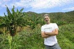Agricoltore organico davanti a terreno coltivabile Fotografia Stock Libera da Diritti
