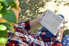 Agricoltore osservando alcuni grafici in una compressa Immagini Stock