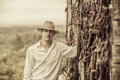 Agricoltore Portrait davanti ad una parete in pieno degli strumenti Immagine Stock