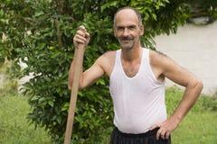 Agricoltore Posed davanti all'albero con la maniglia della zappa Fotografia Stock