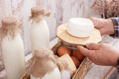 Agricoltore senior abile con i prodotti lattier-caseario freschi Immagine Stock