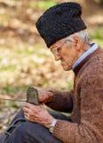 Agricoltore senior che assiste la sua post-utilizzazione della motosega Fotografia Stock Libera da Diritti
