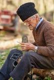 Agricoltore senior che assiste la sua post-utilizzazione della motosega Fotografie Stock