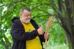 Agricoltore senior che mostra buon raccolto Immagine Stock