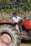 Agricoltore senior che per mezzo di vecchio trattore per arare la sua terra Fotografie Stock