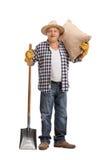 Agricoltore senior che posa con un sacco e una pala Fotografia Stock Libera da Diritti